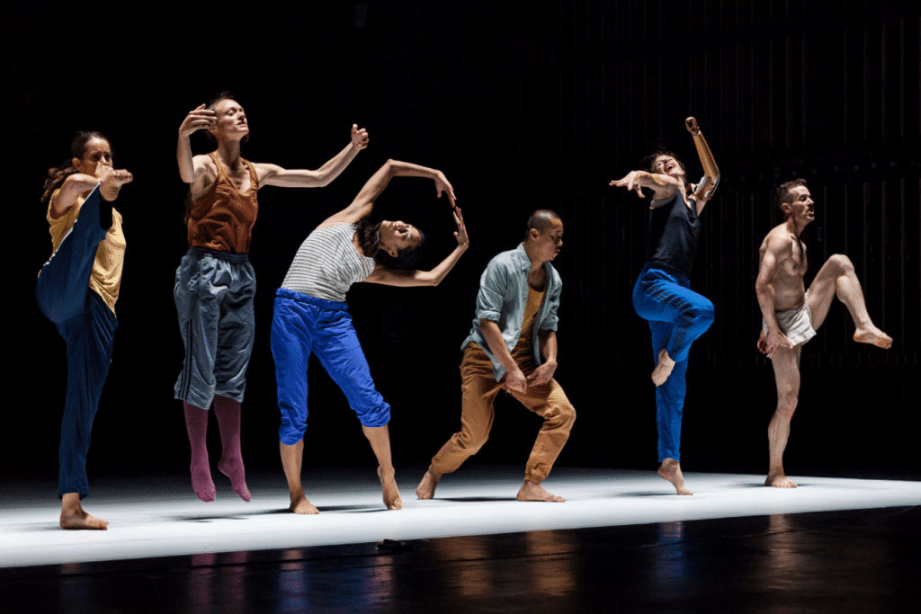 Six dancers, made up of a mix of genders, ethnicity and age, each captured in different poses. The poses are contemporary ballet in style but are partnered with varying levels of eccentric facial expressions.